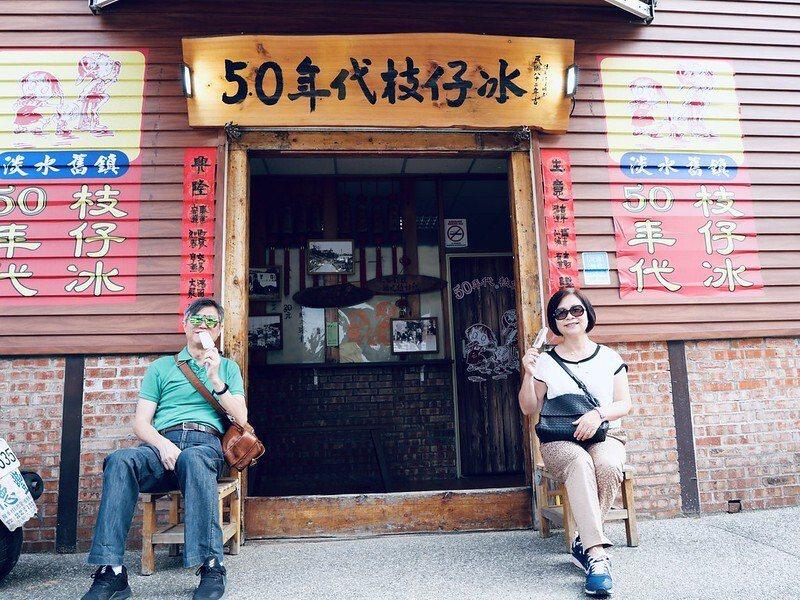 坐在淡水舊鎮50年代枝仔冰前,開心的手上拿著枝仔冰的好友夫婦,古早味的美味已透露在臉上了(本圖事先已獲夫婦倆同意刊登,amy所攝)