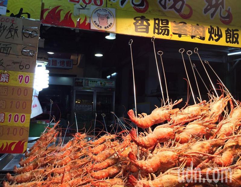 高雄市六合夜市一賣胡椒蝦的攤商因為兼賣香腸炒飯,堅持貼出國產豬肉的標章讓顧客放心食用。記者楊濡嘉/攝影