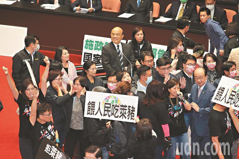 萊克多巴胺豬肉明年將進口台灣,引發爭議。 圖為日前國民黨立委發動「內臟攻擊」反萊豬,在民進黨立委層層護衛下,行政院長蘇貞昌(中)站在備詢台,一度面帶微笑環視四周。本報資料照片