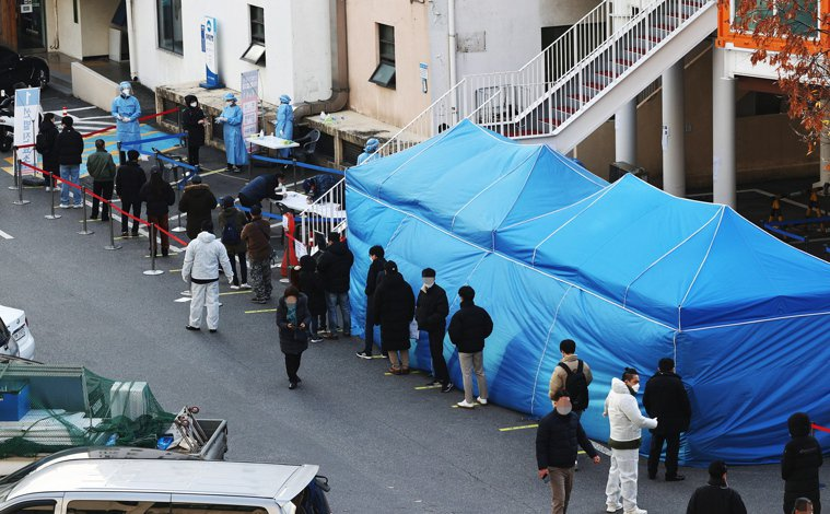 韓國民眾在首爾街頭的臨時檢測站排隊接受新冠肺炎檢測。歐新社