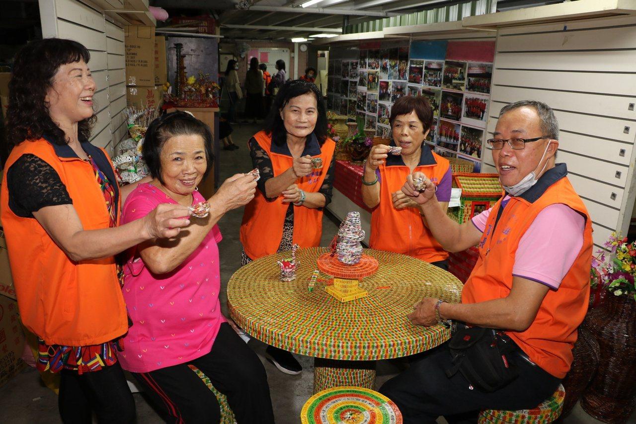 李黃不(左2)與據點內其他長輩,舉起用四色牌做的茶杯作勢喝茶。 圖/王敏旭 攝影