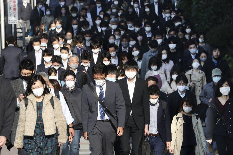 日本通勤的上班族十七日帶著口罩經過東京街頭。(美聯社)