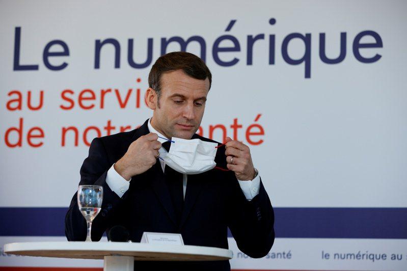 法國總統馬克宏4日視察巴黎一家醫院時戴上口罩。(路透)