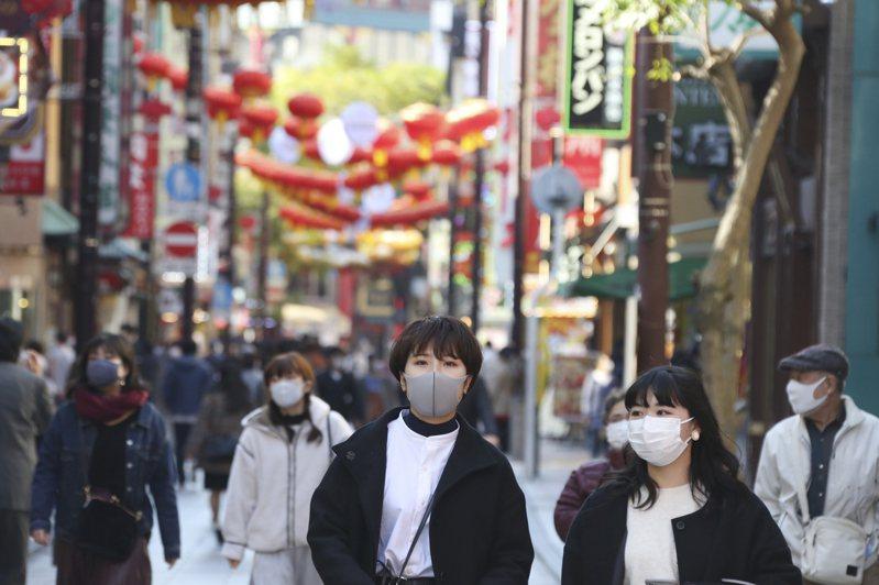 日本神奈川縣行人本月一日戴著口罩經過橫濱中華街街頭。(美聯社)