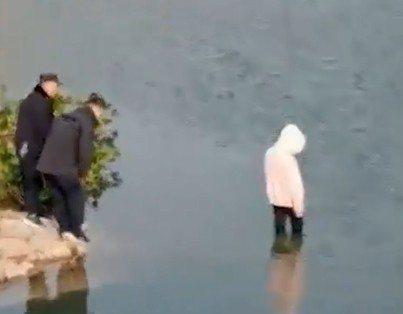 一名穿著白色帽T的女子站在水中,水深到膝蓋處,雖然岸上已有警察待命,且途中不斷進行勸導,但女子仍跳入河中。 圖/瀟湘晨報