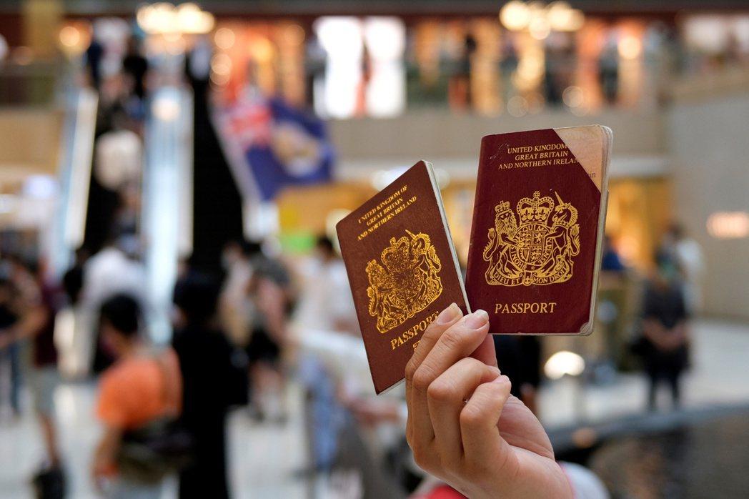 香港一名抗議港版國安法的示威者,拿著英國國民海外護照。(路透)