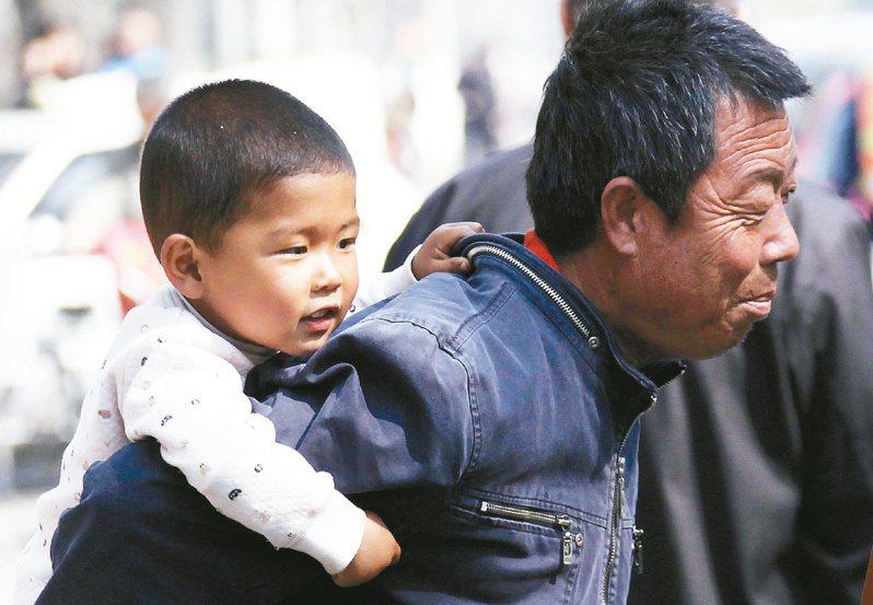 中國家長的優生優育觀念深入人心,但他們的錢只夠培養一個精英。圖為北京一名父親背著孩子行經市區。路透
