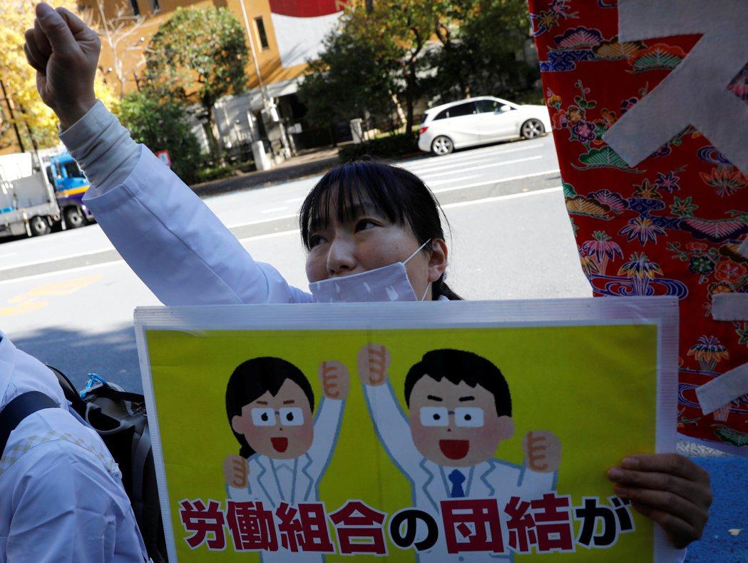 圖為12月4日的東京,民眾戴著口罩高呼口號,支持醫院裡的醫療人員罷工。  圖...