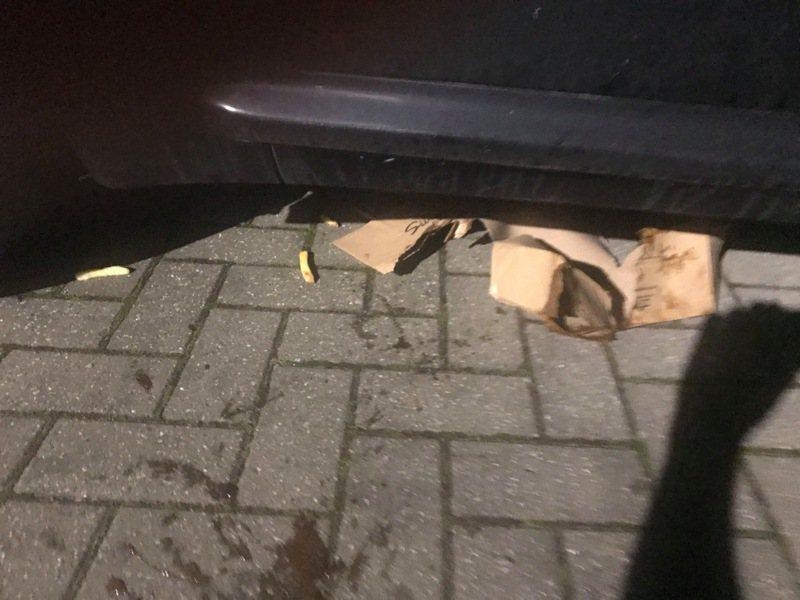 監視錄影畫面顯示,裝著餐點的紙袋突然破掉,但該名外送員竟徒手撿起一地的餐點,並把破掉的袋子踢進汽車底下。 圖/《太陽報》