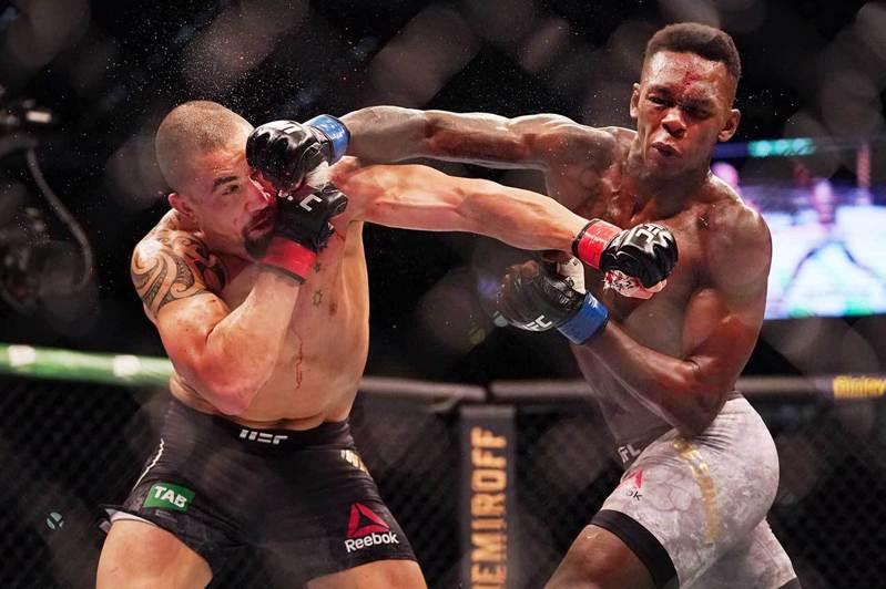 超級新星亞德桑尼亞(右)在去年擊敗拳王惠特克(左),成為新的UFC中量級冠軍。 歐新社資料照片