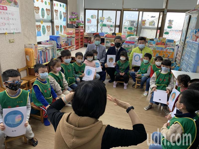 客委會主委楊長鎮(後排左二)、縣長楊文科(後排左一)與10多名小朋友,一起唱跳客家童謠「伯公」,並拿著客語語詞卡玩遊戲。記者陳斯穎/攝影