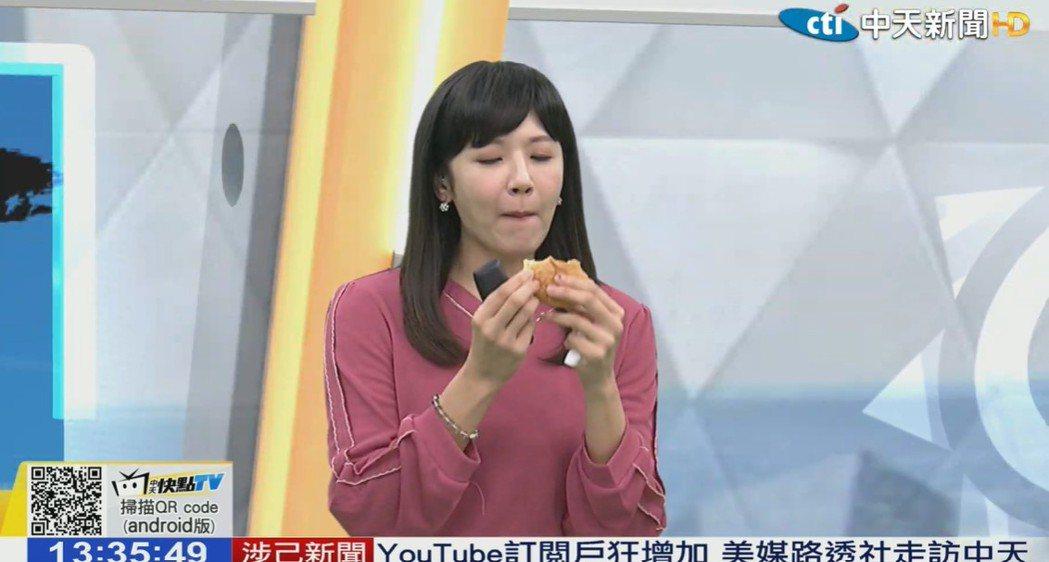 中天主播鄭亦真吃漢堡播新聞。圖/摘自YouTube
