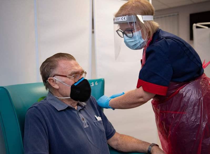 美國企業現僅鼓勵而非強制員工接種新冠疫苗。圖為英國一名護士8日在約克郡謝菲爾德市一家醫院,為民眾注射Pfizer-BioNTech新冠疫苗。法新社