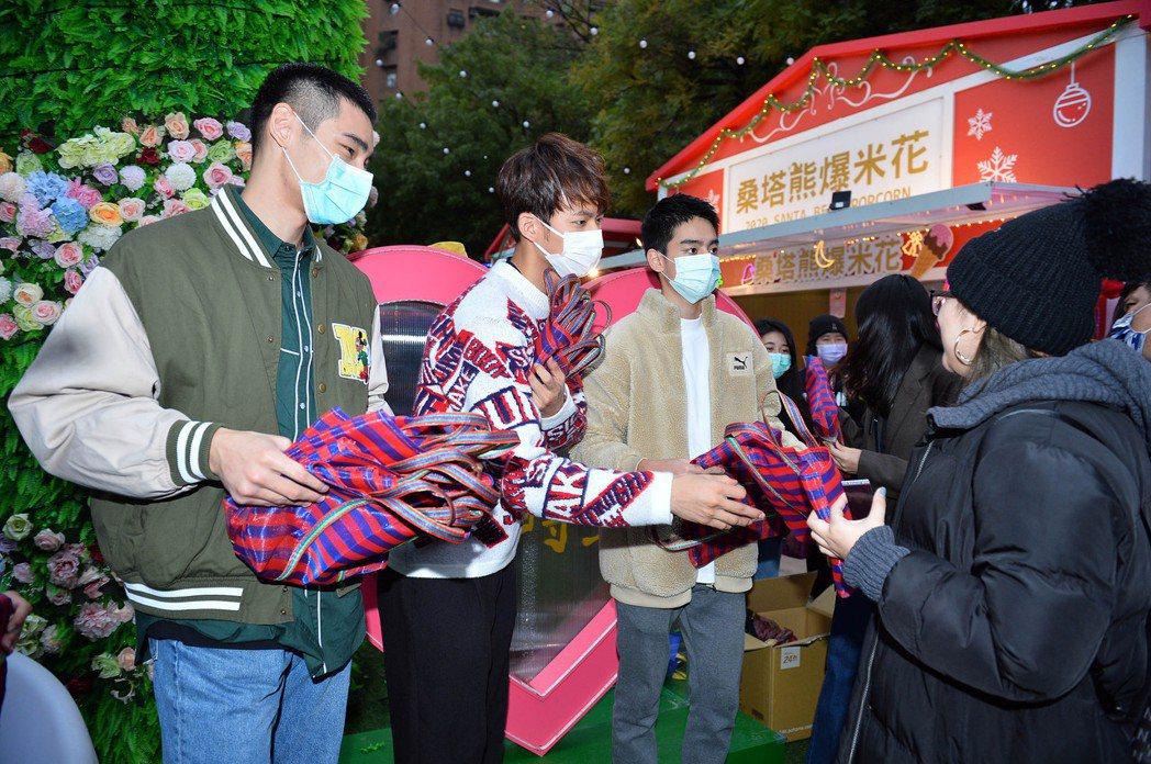 章廣辰(左起)、吳念軒、劉敬在新北歡樂耶誕城發送「粉紅茄芷袋」。圖/TVBS提供