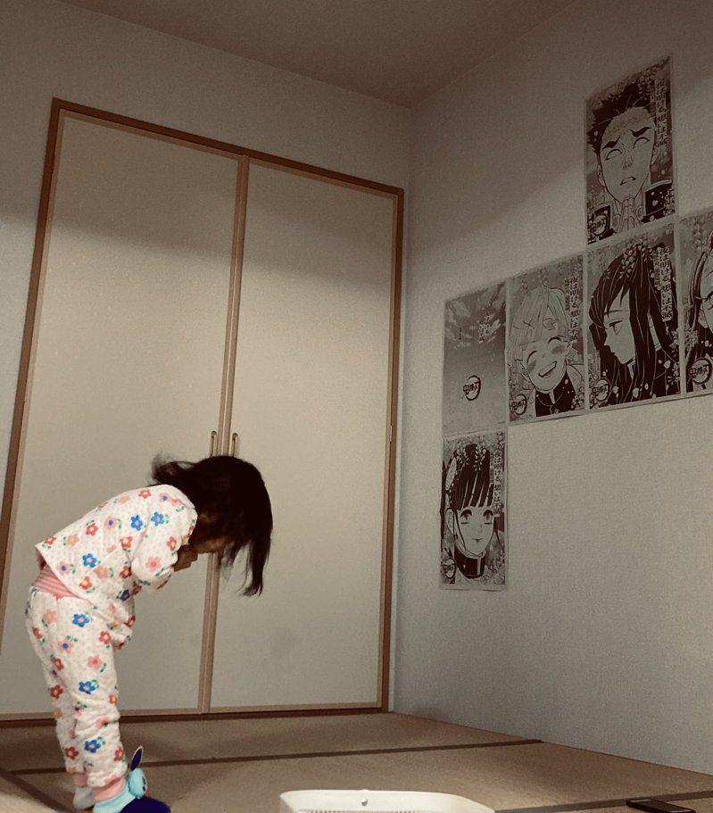 女孩對牆上鬼滅之刃的海報膜拜。圖/取自Twitter