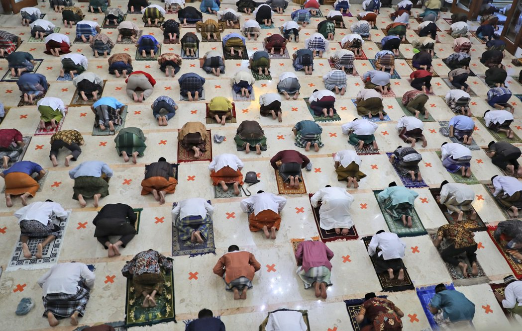 今年開齋節,印尼穆斯林在保持社交安全距離的情況下進行膜拜。 圖/美聯社