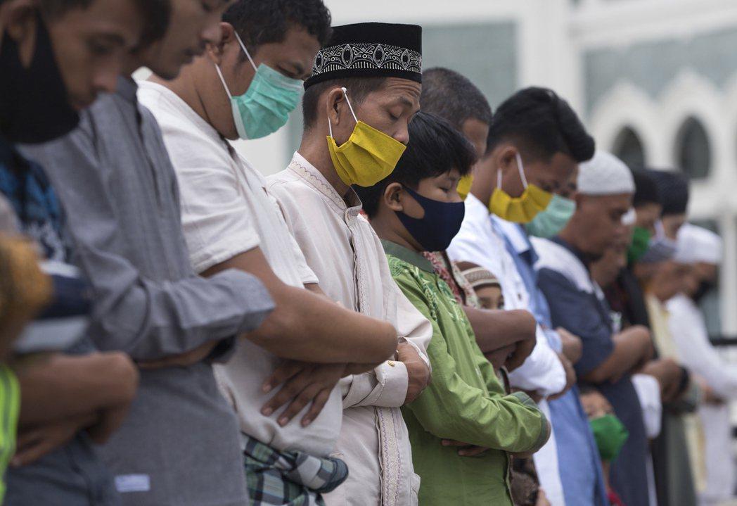 印尼當地民眾們帶著口罩或面罩進行膜拜。 圖/美聯社