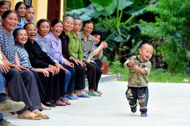 中國的勞動人口平均年齡正在變老。一項報告顯示,1985到2018年間,全國勞動力人口的平均年齡從32.2歲上升到了38.4歲。圖一名小孩從一群老人前面跑過。新華社