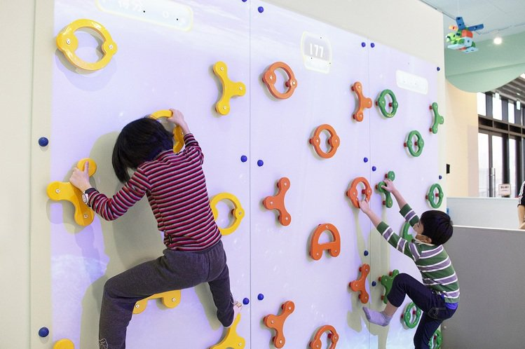 「桃樂比互動遊戲區」有攀岩、畫布積木、趣味桌遊,讓孩子發揮組合與創造的能力。圖/...