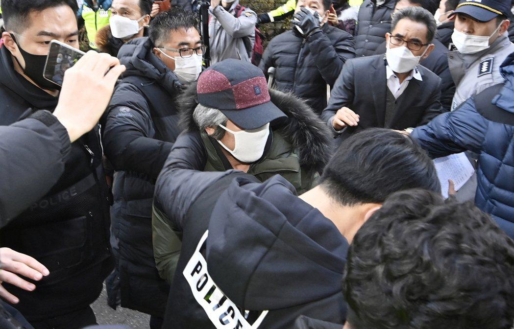 趙斗淳(中)12日出獄回家後尚未外出,圖為當日他在警方戒護下回到安山的家。美聯社