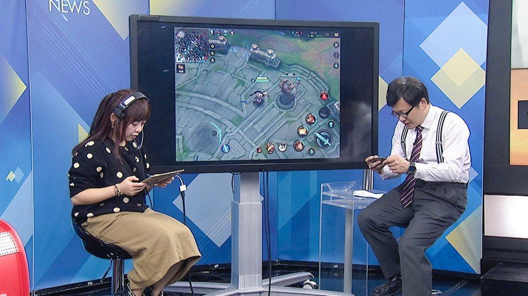 新聞龍捲風主持人戴立綱(右)電玩魂上身,玩手遊慘遭電爆。圖/中天新聞台提供