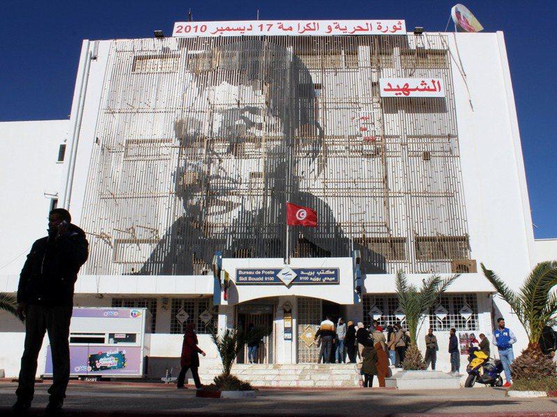 17日是阿拉伯之春運動十周年紀念日。圖為運動發源地──突尼西亞自焚青年布瓦吉吉的故鄉希迪布濟德市,該市郵局本月8日掛出布瓦吉吉巨幅頭像。路透