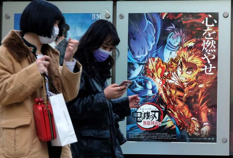 「鬼滅之刃劇場版 無限列車篇」大賣,卻也改變不了日本動畫界的嚴苛環境。圖為東京行人經過戲院海報前。法新社