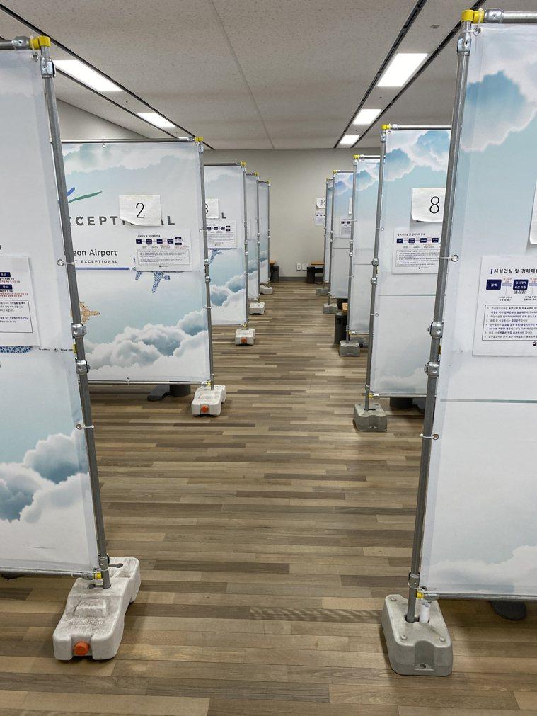 圖為等候分配隔離設施時專用休息室,內部以鐵架及印有仁川機場字樣的帆布隔間。中央社