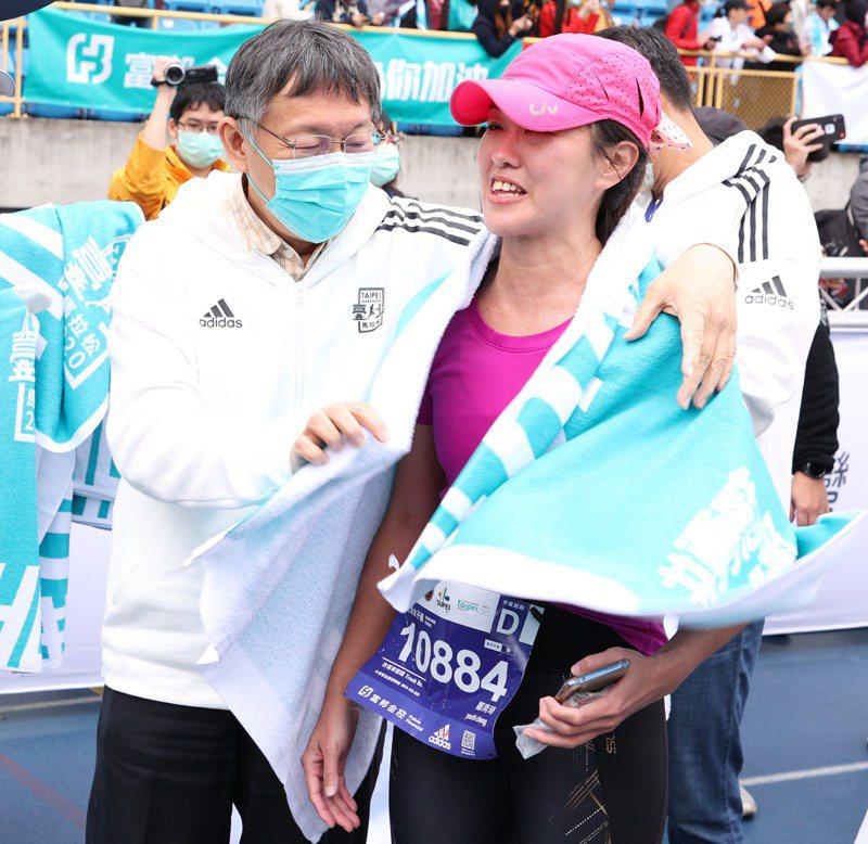台北市長柯文哲(左)出席台北馬拉松比賽,並為完賽選手送上毛巾打氣,。記者葉信菉/攝影
