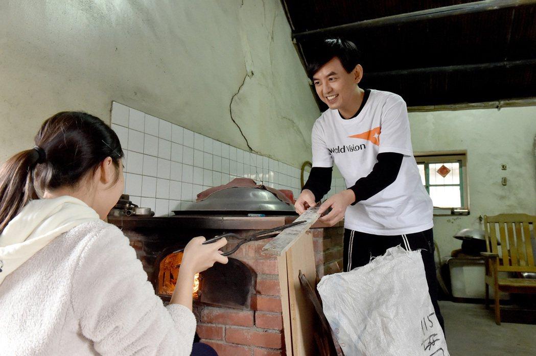 黃子佼(右)幫助小安在沒有熱水器的家添柴燒洗澡水。圖/台灣世界展望會提供