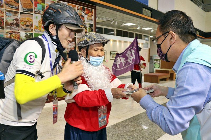 不老騎士單車隊98歲騎士康夢麟(中)送籍給嘉義市社會處長林家緯(右)等人。圖/市府提供
