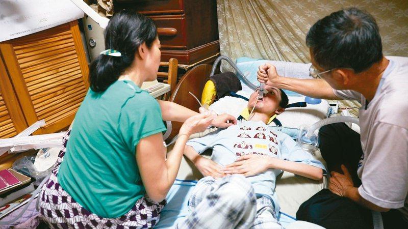 一名肌肉逐漸萎縮的裘馨氏肌肉失養症青年,因為有咳痰機,讓他不會被濃濃的口水嗆著,免於氣切,可以呼吸。圖/罕見疾病基金會提供