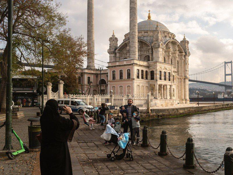 外籍遊客六日和伊斯坦堡的奧塔科伊清真寺合照,土國警方的車則停在一旁巡視有無違規民眾。紐約時報