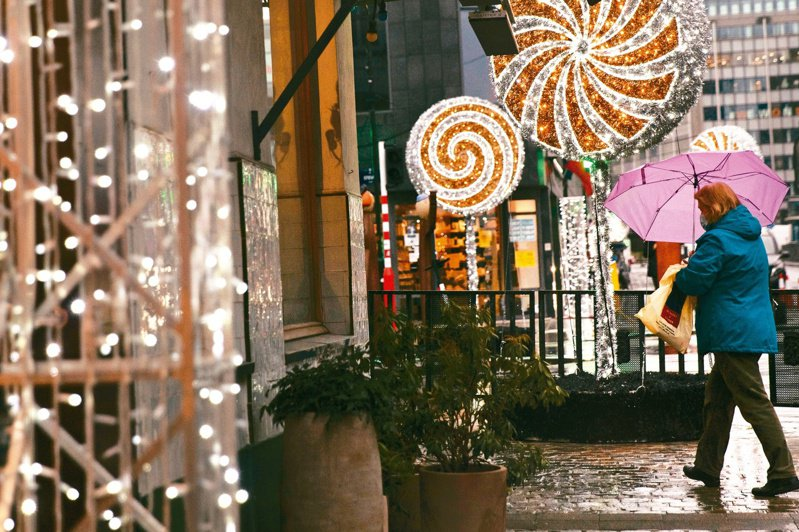 一名撑伞女子廿三日走过布鲁塞尔欧盟总部附近的耶诞装饰。欧盟和英国仍在谈判,希望耶诞节前谈成贸易协议。(美联社)(photo:UDN)