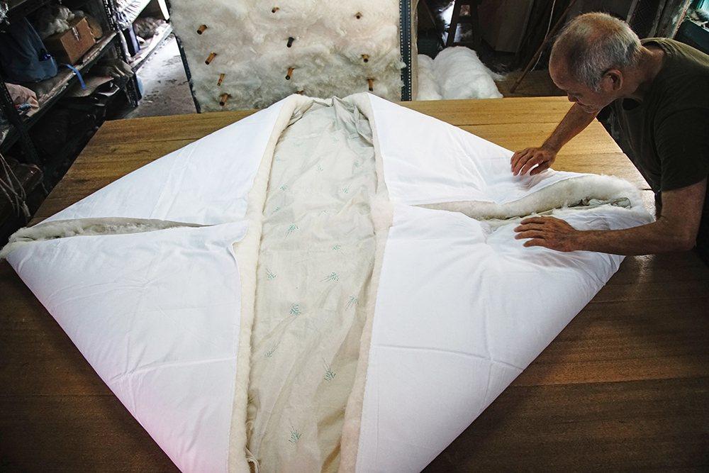 陳君明折起鋪好的棉花,就像變魔術一般,才兩三下就完成翻被。  圖/曾信耀 攝影