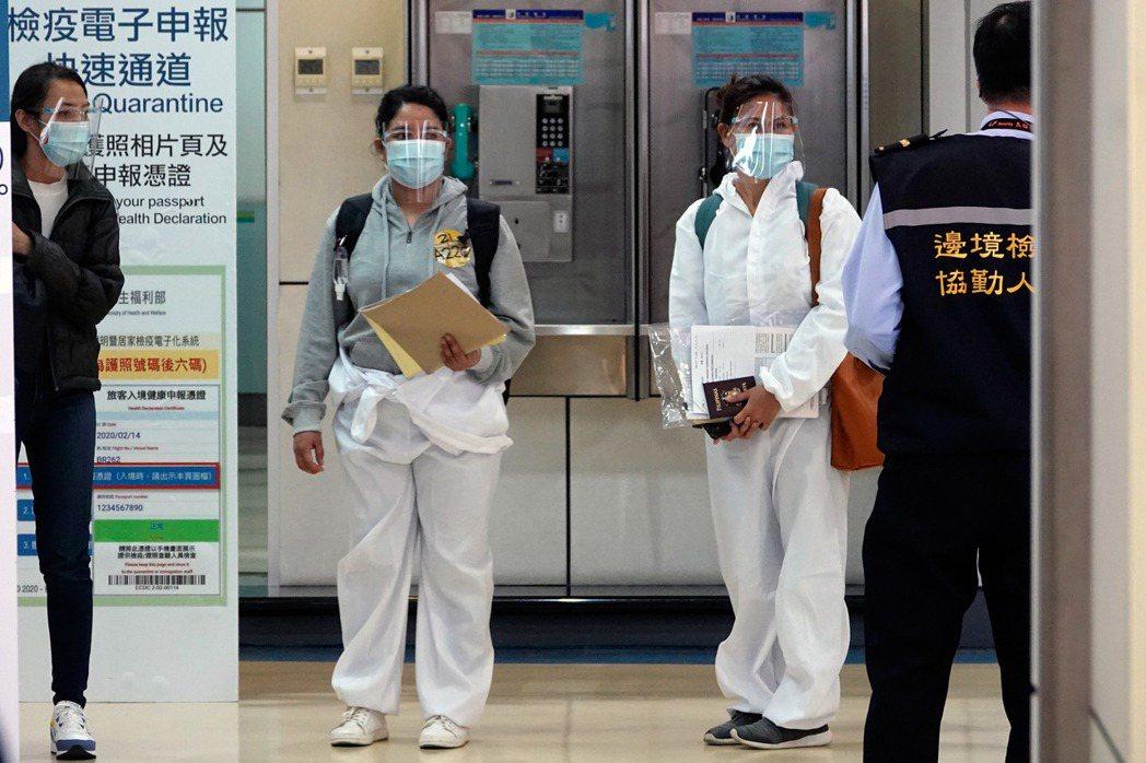 11月30日,兩名外籍移工在桃園機場排隊等候集中核實入境電子健康聲明的資料。 圖/聯合報系資料照