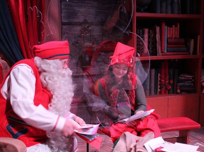 新冠疫情肆虐之下,耶誕老人也得做好防疫措施,圖為17日耶誕老人村里的耶誕老人隔著塑膠板念著信件畫面。法新社