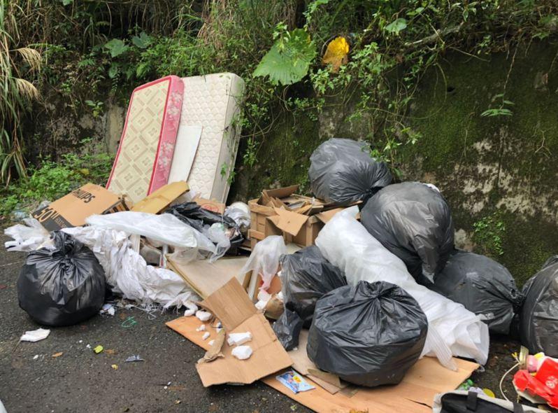 基隆市七堵區大成街旁空地遭棄物出現床墊、空紙箱和數大袋廢棄物,環保局查出搬家公司所為,依廢棄物清理法開罰。圖/基隆市環保局提供