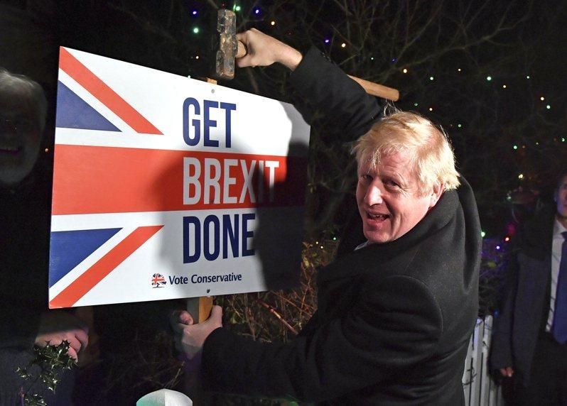 英國與歐盟在24日耶誕夜前宣布達成歷史性的貿易協議,為英國脫歐後的未來雙邊貿易關係定調。圖為11日英國首相強生手扶一塊寫著「完成脫歐」的牌子。(美聯社)