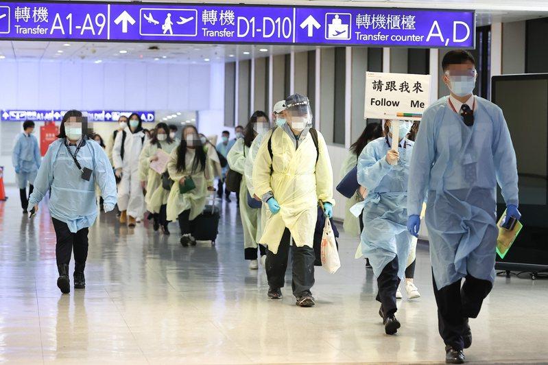 為防範英國來的變種新冠肺炎病毒入侵,機場規劃專屬動線給114名從英國回台的旅客,由工作人員以十人一組帶隊前往通關入境。記者季相儒/攝影