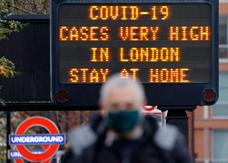 倫敦市中心的行人走過路標,提醒人們「疫情很嚴峻,待在家裡」,其中一些人戴著口罩。圖╱法新社