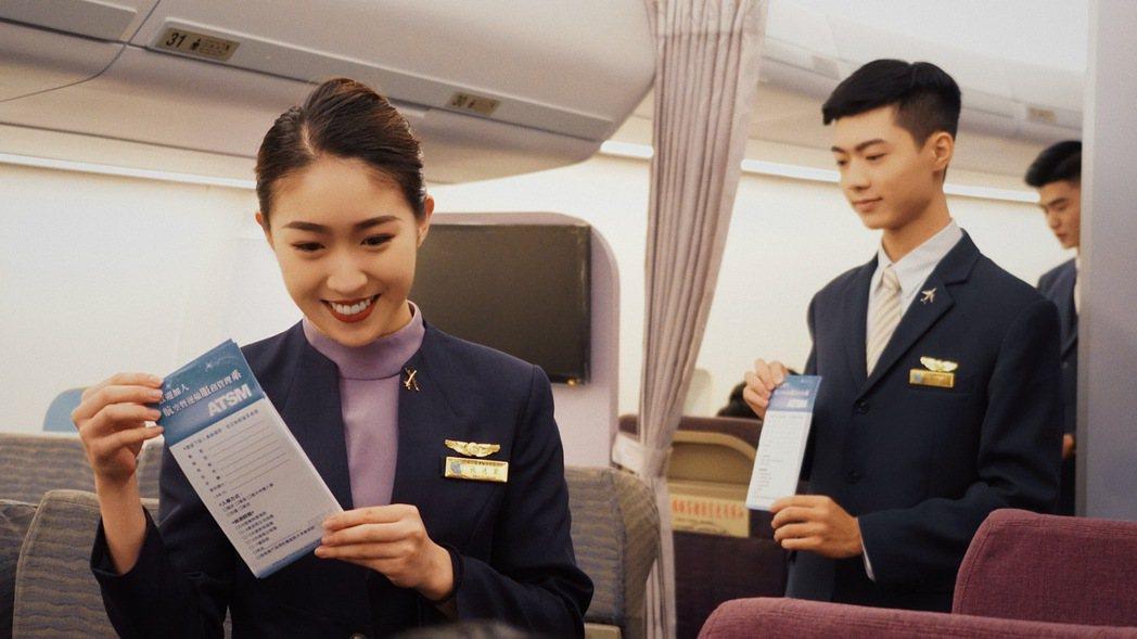 航服桌曆三月人物-學生董愷琦(左)與朱容皜向旅客發放入境表格。 萬能科大/提供。