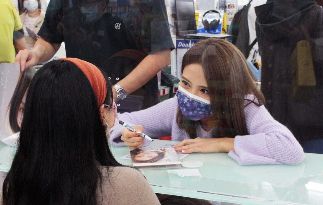 李宣榕(右)隔著板子跟粉絲簽名、合照。圖/福茂唱片提供