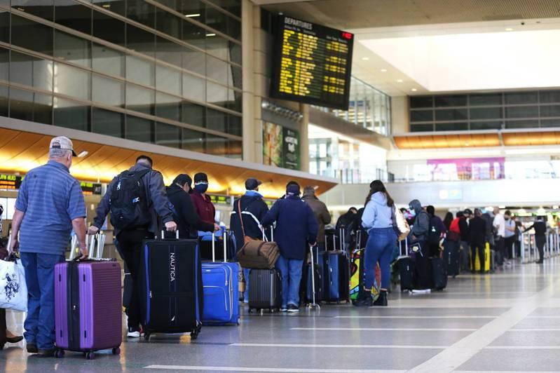 美國洛杉磯疫情拉警報,近日衛生機關下令提升檢疫規格。圖為上月洛杉磯機場內大排長龍等待報到的旅客。法新社