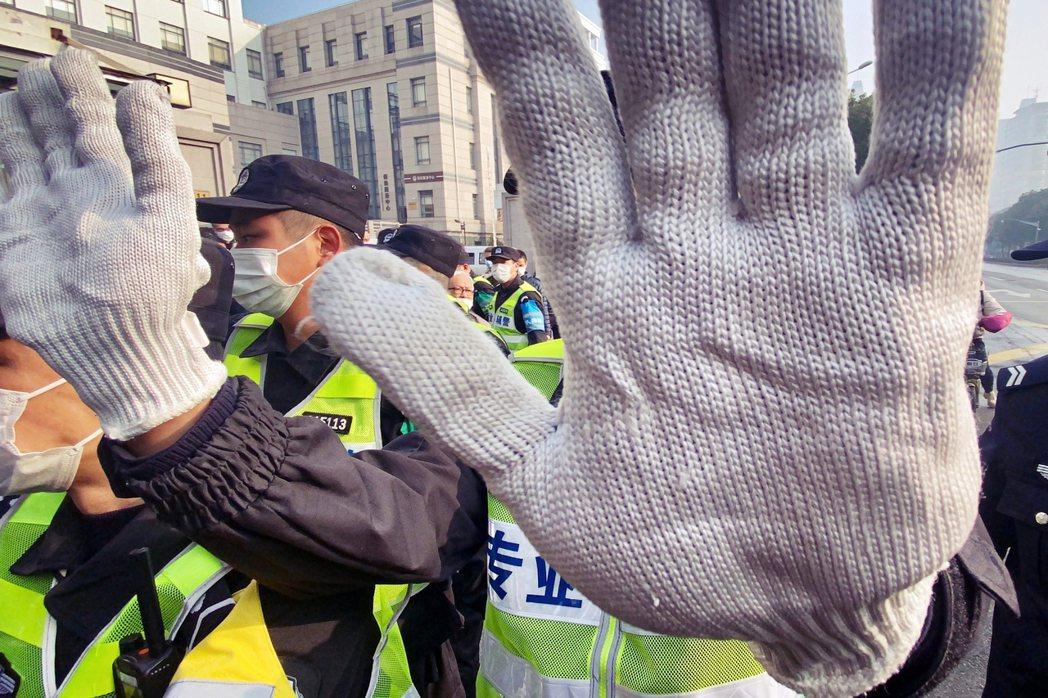 法庭外阻止媒體拍攝的中國輔警。圖/法新社