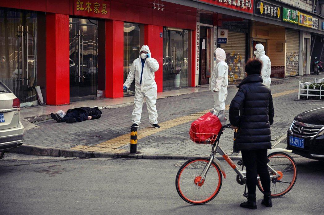 2020年1月30日,疫情最嚴峻時、武漢街頭有人當街倒下。圖/法新社
