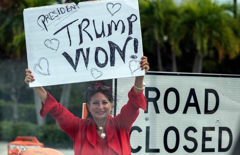 大選結束至今,仍有部分挺川選民對結果憤恨不平,或備感失落。圖為30日在佛州西棕櫚郡一川粉在川普車隊經過的路邊高舉「川普贏了」的標語。 法新社
