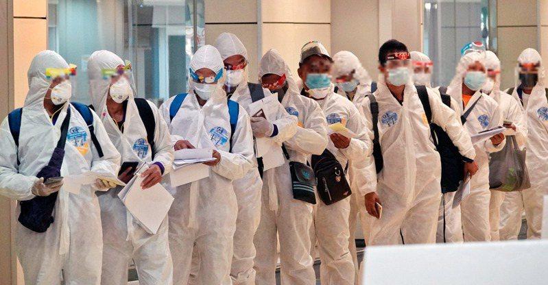我國出現首例英國變種病毒確診個案,指揮中心昨緊急宣布,自明年元旦零時起(當地搭機時間),限縮非本國籍人士入境及檢疫規定。圖為身穿隔離衣的外國人士入境桃園機場,等待檢疫。記者鄭超文/攝影