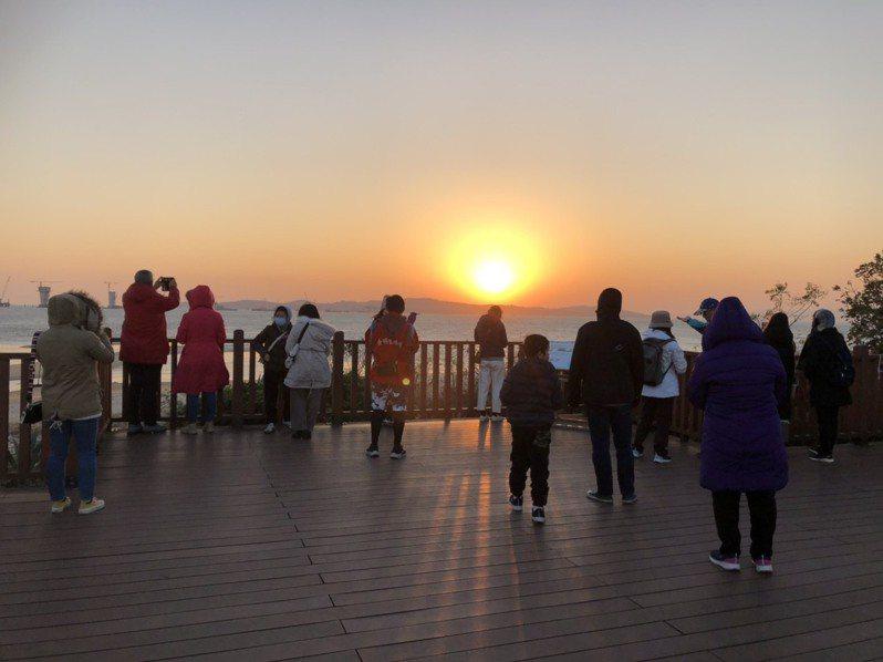 為了欣賞2020年金門最後一道夕陽,不少台灣的遊客到慈堤追日,大家爭相拍下夕陽沒入海面的瞬間。記者蔡家蓁/攝影