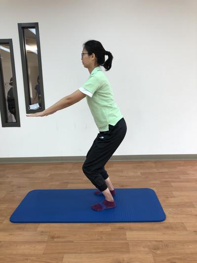 站姿踮腳腳踝穩定訓練:雙膝微蹲,背部打直,雙手向前伸直維持平衡。圖/周昭如提供